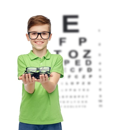 eye chart: happy smiling boy in green polo t-shirt with eyeglasses over eye chart background