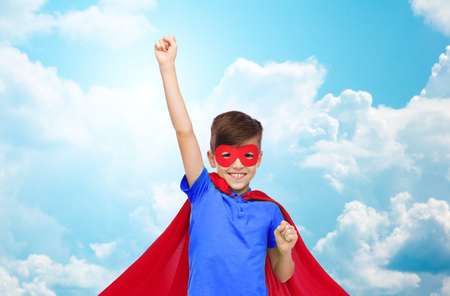 happy boy in red superhero cape and mask showing fists over blue sky and clouds background Stock Photo