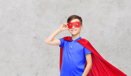 pre teen boy: happy boy in red superhero cape and mask over gray concrete background