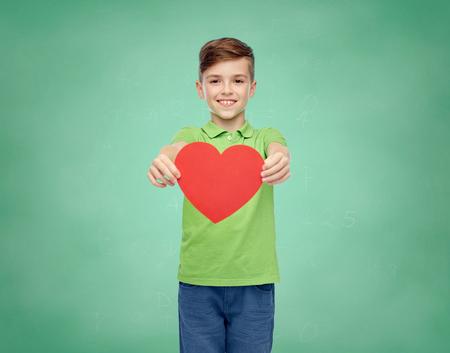 pre teen boy: happy smiling boy in green polo t-shirt holding blank red heart shape over green school chalk board background