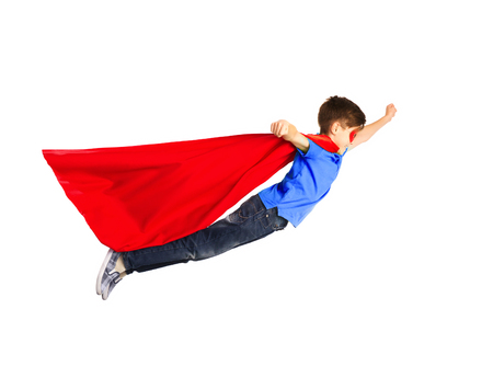 boy in red superhero cape and mask flying in air