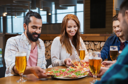 pizza: smiling friends eating pizza and drinking beer at restaurant or pub