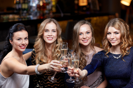 hen party: happy women with champagne glasses at night club