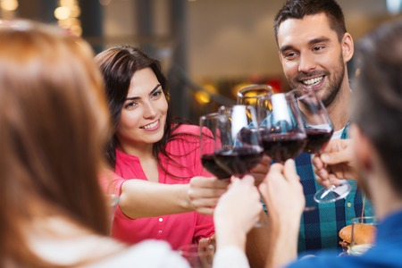 cheers: happy couple and friends clinking glasses of wine at restaurant