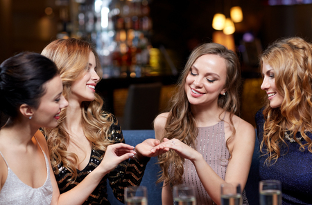 hen party: happy woman showing engagement ring to her friends with champagne glasses at night club