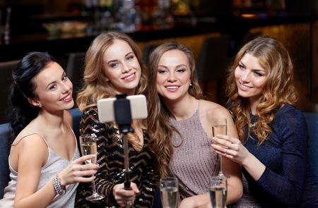 night stick: happy women with champagne and smartphone selfie stick taking picture at night club