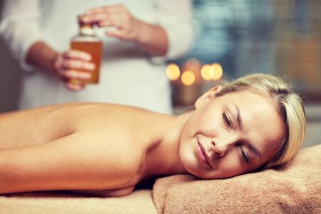 massagist: close up of beautiful young woman lying with closed eyes on massage table and therapist holding oil bottle in spa Stock Photo