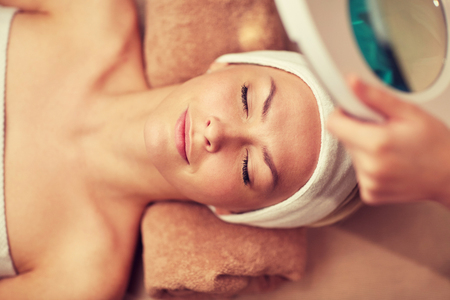 cosmetologist: close up of beautiful young woman lying with closed eyes and cosmetologist looking through magnifying lamp in spa Stock Photo