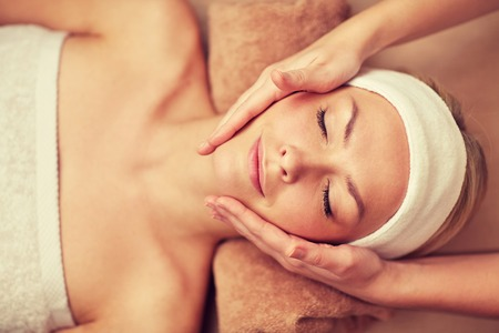 close up of beautiful young woman lying with closed eyes having face massage in spa