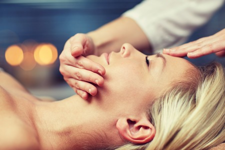 head massage: close up of beautiful young woman lying with closed eyes and having face or head massage in spa Stock Photo