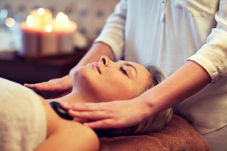masajes relajacion: Cerca de la mujer joven hermosa que tiene masaje con piedras calientes en el spa Foto de archivo