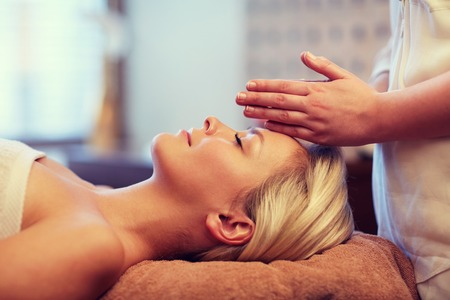 massagist: close up of beautiful young woman lying with closed eyes and having face or head massage in spa Stock Photo