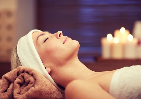 close up of beautiful young woman lying with closed eyes in spa