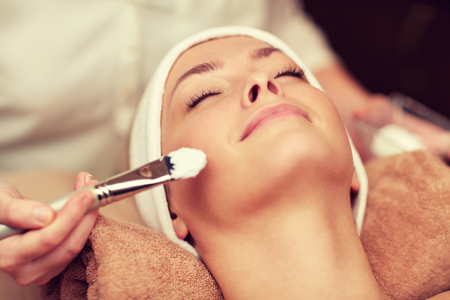 cosmetologist: close up of beautiful young woman lying with closed eyes and cosmetologist applying facial mask by brush in spa