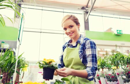 smiling woman in a greenhouse: happy woman or gardener holding flowers in greenhouse