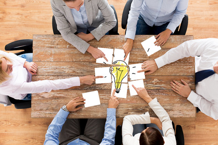 business, office people, startup and teamwork concept - close up of creative team sitting at table and putting together puzzle pieces with light bulb picture