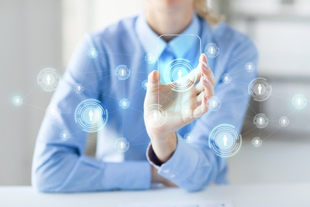 business contact: business, technology, social network and people concept - close up of woman hand holding and showing transparent smartphone with contact icons on screen at office