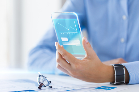 business, technology and people concept - close up of woman hand holding transparent smartphone with chart on screen at office Stock Photo