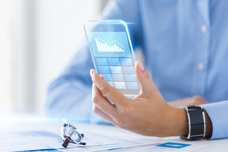 charts graphs: business, technology and people concept - close up of woman hand holding transparent smartphone with chart on screen at office