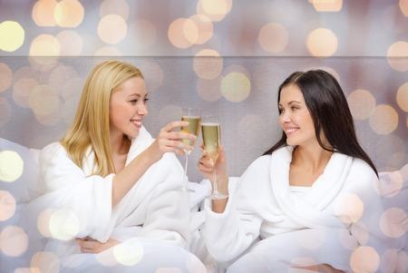 Reisen, Feiern, Freundschaft und Ferien-Konzept - lächelnde Freundinnen in Bademäntel mit Champagnergläsern im Bett im Hotel über Lichter Hintergrund
