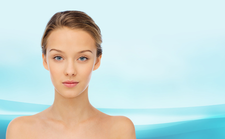 beauty, people and health concept - young woman face and shoulders over blue wavy background