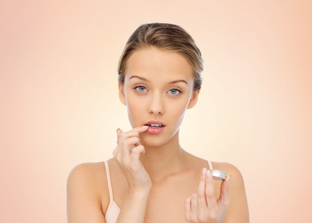 beauty, people and lip care concept - young woman applying lip balm to her lips over beige background Stock Photo