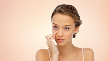 schoonheid, mensen, cosmetica, huidverzorging en gezondheid concept - jonge vrouw die room toepast op haar gezicht over beige achtergrond Stockfoto