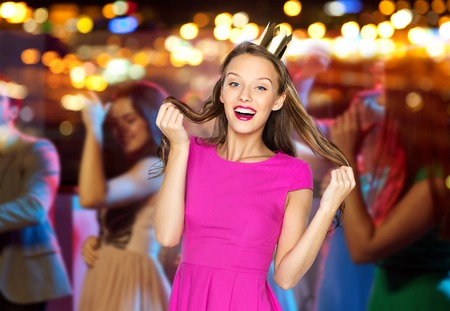 people, holidays, celebration and glamour concept - happy young woman or teen girl in pink dress and princess crown at night club party over crowd and lights background