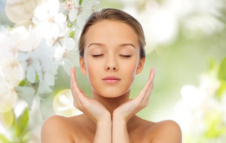 beauty, people, skincare and health concept - young woman face and hands over cherry blossom background