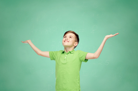 pre adolescent boy: childhood, achievement, gladness and people concept - happy smiling boy in green polo t-shirt raising hands and looking up over green school chalk board background