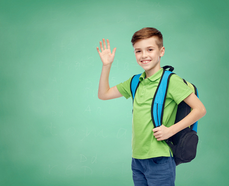 childhood, school, education, greeting gesture and people concept - happy smiling student boy with school bag waving hand over green school chalk board background