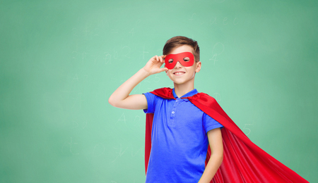 pre adolescent boys: education, childhood, power and people concept - happy boy in red superhero cape and mask over green school chalk board background
