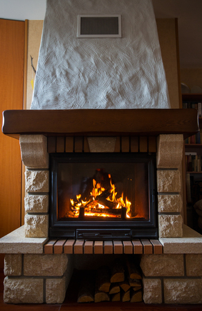 cosiness: heating, warmth, fire and cosiness concept - close up of burning fireplace at home
