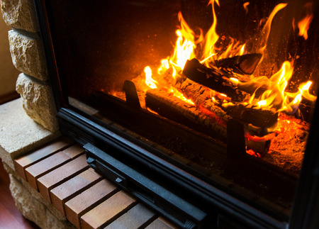 wood and fire: heating, warmth, fire and cosiness concept - close up of burning fireplace at home