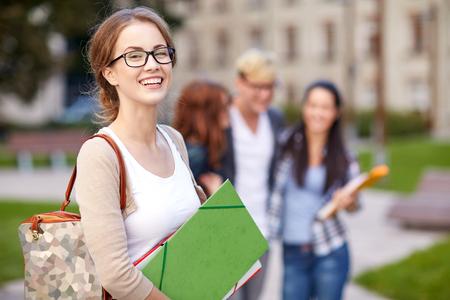 la educación, la escuela, la amistad y el concepto de la gente - grupo de estudiantes adolescentes felices con las carpetas de la escuela