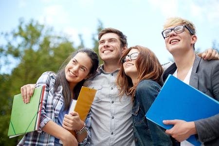 amistad: la educación, la amistad, el futuro y el concepto de adolescente - grupo de estudiantes felices con las carpetas que miran para arriba en el campus o parque