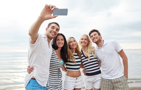 family beach: summer, sea, tourism, technology and people concept - group of smiling friends with smartphone on beach photographing and taking selfie