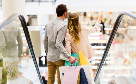 shopping: la venta, el consumo y el concepto de la gente - feliz pareja joven con bolsas de la compra que va abajo por la escalera mecánica y que señala el dedo en el centro comercial