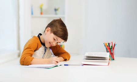 education, childhood, people, homework and school concept - smiling student boy with book writing to notebook at home Standard-Bild