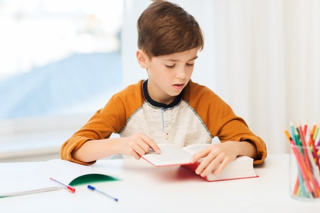 child sitting: education, childhood, people, homework and school concept - student boy reading book or textbook at home