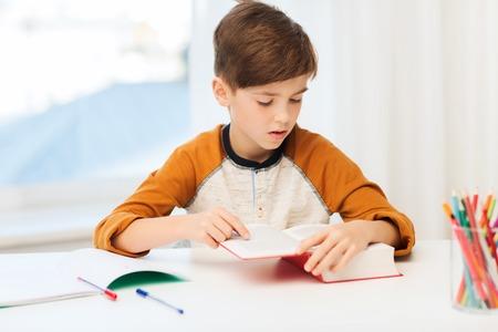 personas leyendo: la educación, la infancia, las personas, la tarea y la escuela concepto - muchacho del estudiante libro o libro de texto de lectura en el hogar Foto de archivo