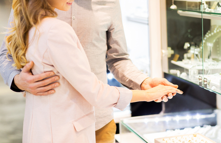 diamond ring: sale, consumerism, shopping and people concept - close up of happy couple choosing engagement ring at jewelry store in mall Stock Photo