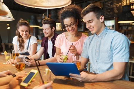 人、レジャー、友情およびコミュニケーション概念 - タブレット pc コンピューターとドリンクと幸せな笑みを浮かべて友達のグループ バーやパブ