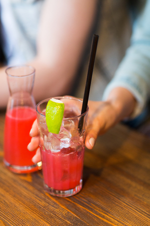 degustating: leisure, drinks, people and holidays concept - close up of woman hand holding glass of fruit juice or cocktail with straw and ice Stock Photo