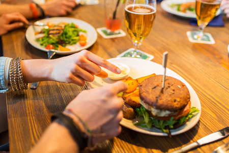 people, leisure, friendship, eating and food concept - close up of friends hands with burger at bar or pub Фото со стока