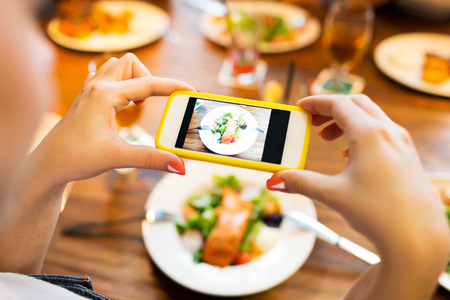 photographing: people, leisure, technology and internet addiction concept - close up of woman with smartphone photographing food at restaurant