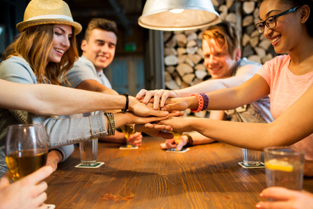 party friends: people, leisure, friendship and gesture concept - group of happy smiling friends with drinks putting hands on top of each other at bar or pub