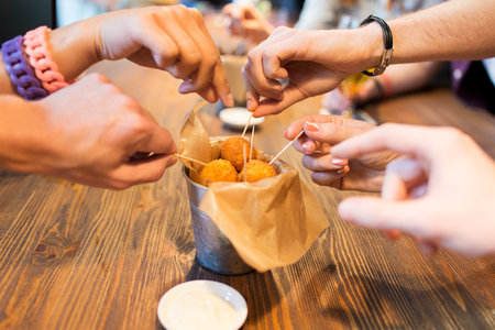 fried food: fast food, junk food, unhealthy eating and culinary concept - close up of people hands taking cheese balls with skewers at bar or restaurant Stock Photo