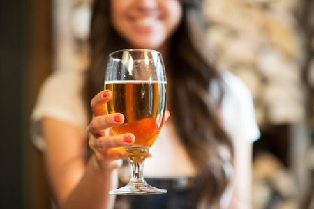 non alcoholic beer: leisure, drinks, degustation, people and holidays concept - close up of smiling woman hand holding glass of draft lager beer Stock Photo