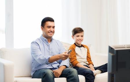 ver tv: la familia, las personas, la tecnología, la televisión y el concepto de entretenimiento - feliz padre e hijo con mando a distancia viendo la televisión en casa Foto de archivo